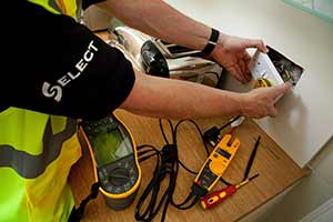 A SELECT electrician fitting a plug