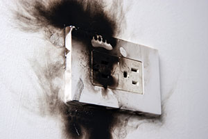 Electrical professionals dealing with a plug fire overload
