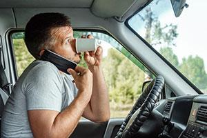 A man drinking coffee and on his phone whilst driving for work